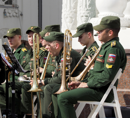 aerophone: Trumpeters in anticipation for his musical part. Brass band playing on the Central Avenue in the Park of VDNH. International Military Music Festival Spasskaya Tower.