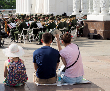 aerophone: A pre-adolescent girl and a pair of young men seated on the parapet during a performance of the brass band. Central Avenue in the Park of VDNH, Moscow. International Military Music Festival Spasskaya Bashnya.