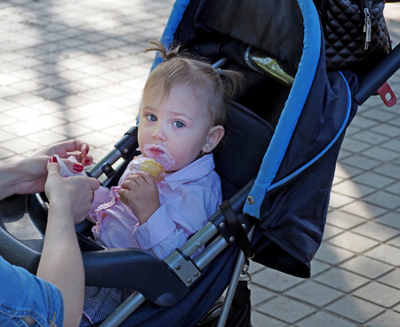 eat smeared baby: Smeared with ice cream elementary age girl in a pram on a city street