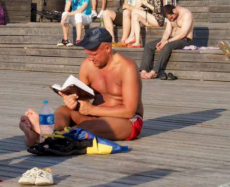 duckboards: Heat in Moscow. Sunbathing mid adult man reading a book sitting on the wooden flooring. Dry fountain at the Crimean waterfront.