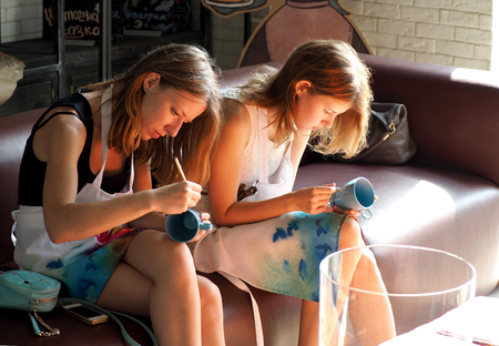 Two late teens girls painting on mugs. Free activities for adults and children in Moscow.