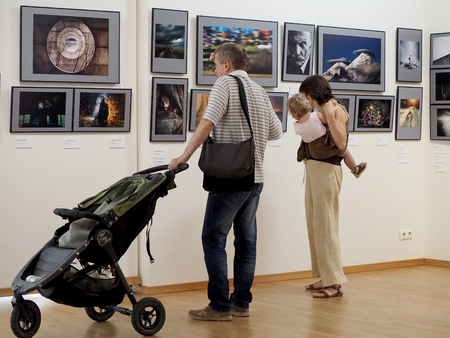 elementary age girl: Family with elementary age girl and pram in a gallery. Classic Photo Gallery. Russian Week Of Photography 2016