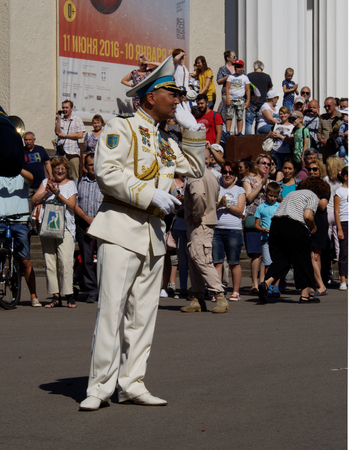 aerophone: Bandmaster of  brass band from Kazakhstan asks the audience what musical composition to perform. Festival of military orchestras Spasskaya Tower. Central Avenue in the Park of VDNH, Moscow.