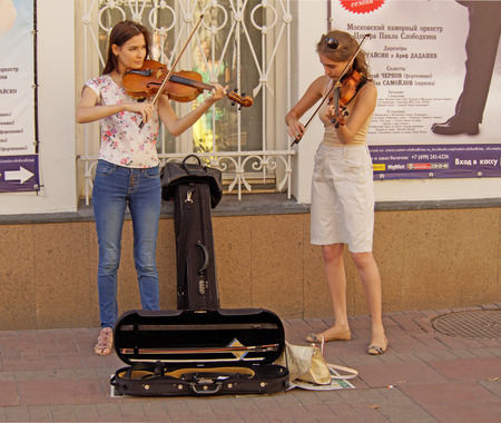 violins: Two young women street musicians playing violins on the street sidewalk