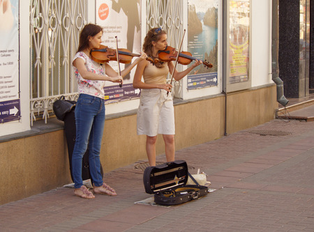 violins: Two young women students playing violins on the sidewalk of Arbat street, Moscow