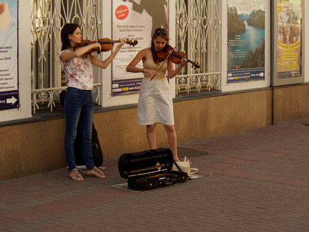 violins: Two young women students playing violins on the walking street Arbat, Moscow Editorial