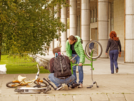 pawn adult: Man in the squatting position with a backpack with two umbrellas corrects the malfunction of an inverted bicycle in the park Museon, Moscow. Standing mid adult woman watching his actions Editorial