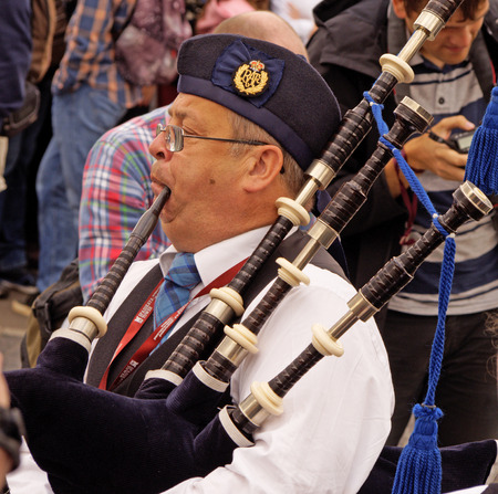 aerophone: Piper of Celtic pipes and drums band  in the crowd in the Park of arts Muzeon on the Crimean embankment, Moscow. Festival of military orchestras Spasskaya Tower.
