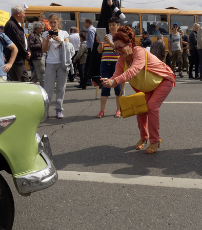 zealously: Bent woman studiously photographing an retro car Editorial