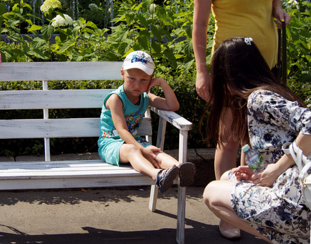 sympathize: Frustrated elementary age boy sitting on a park bench, and mother sympathize with him