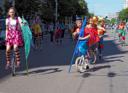 circus performers: Young circus performers on unicycles in the city street on the Parade of street theatres in Voronez Editorial