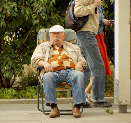Senior adult man slumbering in a chair on the street sidewalk