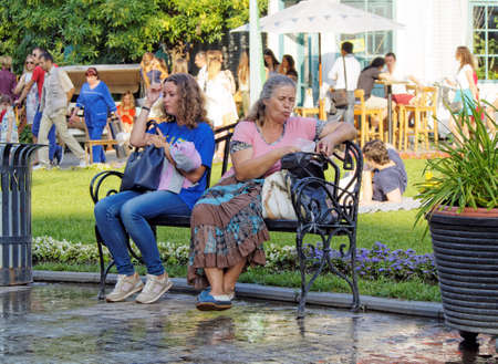 Moscow, Russia - June 19, 2016: An adult chestnut-coloured hair girl and a middle age woman resting on a bench in a city Park 新闻类图片