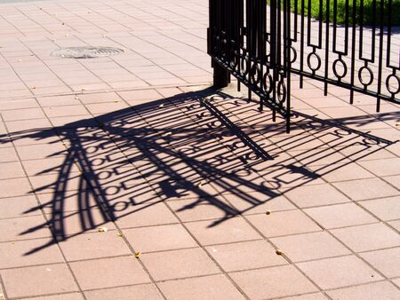 The metal gate and fence and its shadow on the sidewalk
