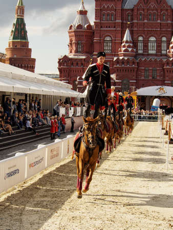 Moscow, Russia - Sep 3, 2016: A group of riders in Circassians and papakhas performs a trick riding standing on Bay horses near the State Historical Museum. Festival Spasskaya Tower Editöryel