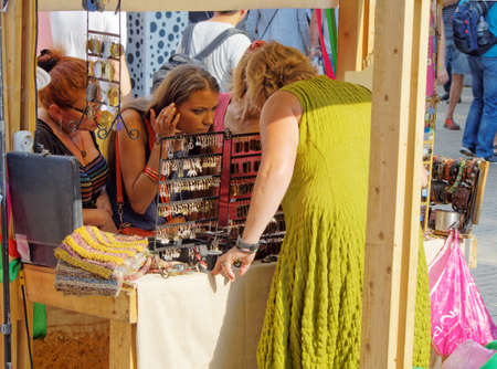 Moscow, Russia, aug 21, 2016: Women look at earrings and other jewelry on the street sale table