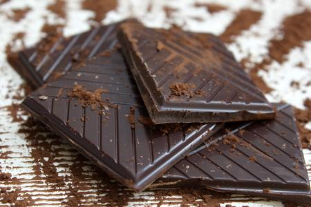 chocolate powder: pieces of dark chocolate with chocolate powder Stock Photo