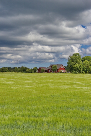 estonian: cloudy sky over traditional estonian rural house
