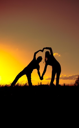 depict: two silhouettes of children on sunset depict a heart shape Stock Photo