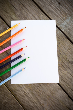 paper sheet: Color pencils on white paper background. Wooden background. Copy space.