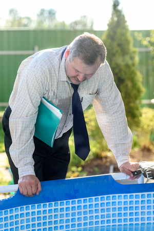 businessman with the folder under the arm looks to the pool Stockfoto