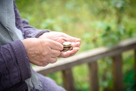 Pieniądze, monety, babcia na emeryturach i koncepcja minimum na życie - w rękach starej kobiety to za mało pieniędzy. Zdjęcie Seryjne