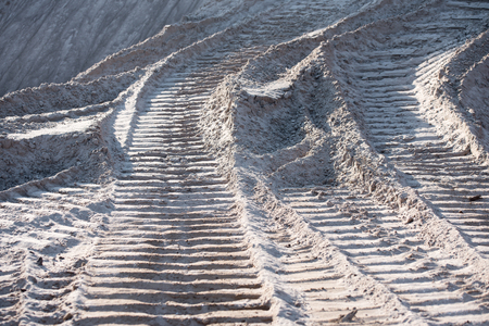 Traces of tires on the surface of a sand pit - the concept of a quarry