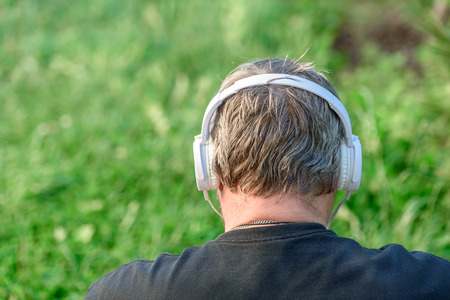 Man with headphones view from behind in the nature, sunny Stok Fotoğraf