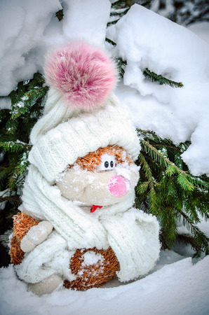 A toy cat sits under a tree in the snow Stok Fotoğraf