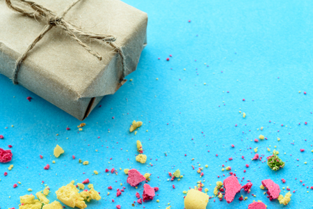 Blue background with gifts and crumbs of a multi-colored cake, t