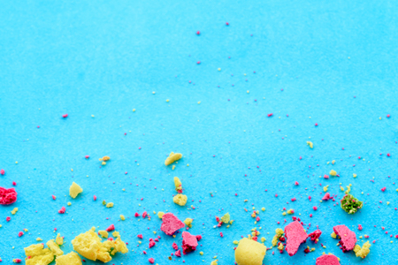 Blue background with multicolored cake crumbs, top view 스톡 콘텐츠