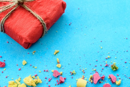 Blue background with gifts and crumbs of a multi-colored cake