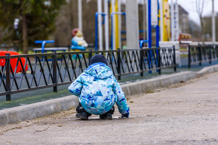 The child plays on the playground, a view from the back Stok Fotoğraf