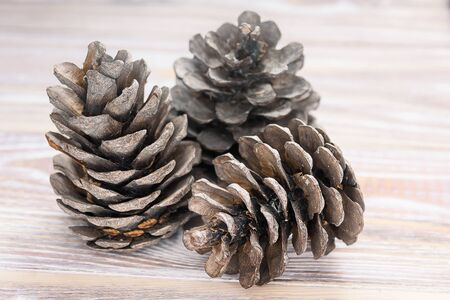 Fir cones on a wooden background.