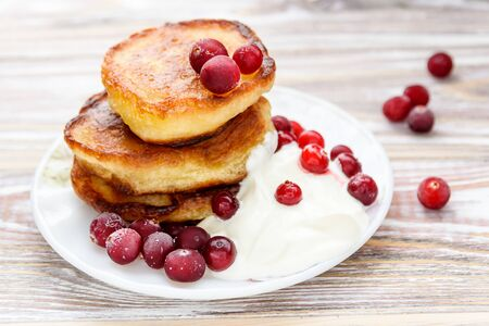 Pancakes with berries and sour cream on a plate. Summer cottage of Russian delicacies