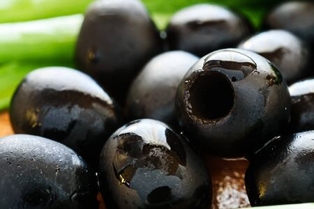 Marinated black olives on wooden background