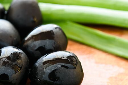 Marinated black olives on wooden background Standard-Bild - 128195880
