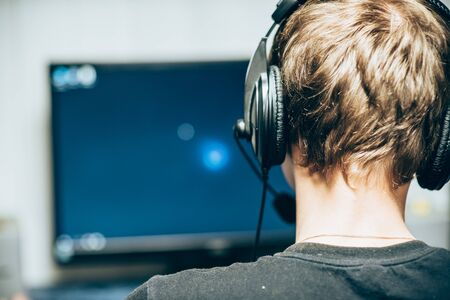 Guy in headphones sitting at the computer view from the back, close-up. Young gamer playing video games