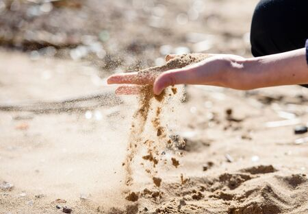 Hand is pouring coral sand on a beach