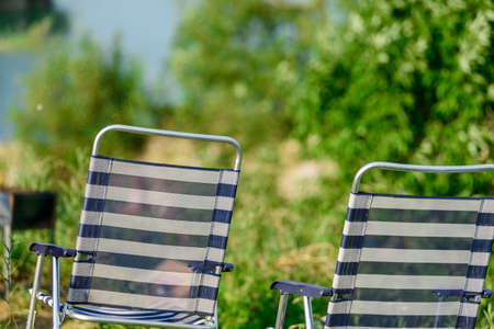 Two folding striped chairs for outdoor recreation