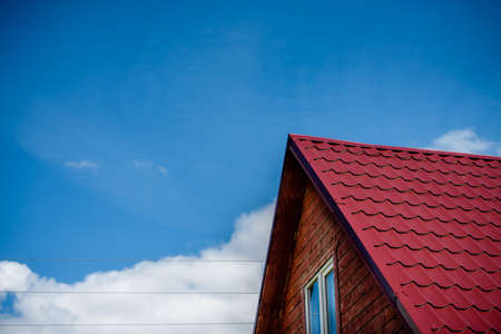 Roof top with red  roof tiles against blue sky