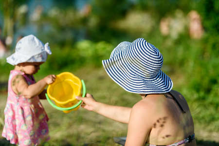 Russia, Saint Petersburg, June 24, 2020: a Mother in a hat and a little daughter relax on the lake in summer