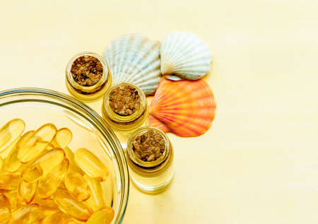 Golden fish oil capsules on a yellow background - the concept of health and natural marine vitamins.