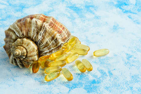 Golden fish oil capsules on a blue background - the concept of health and natural marine vitamins.