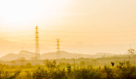 Energy Distribution Network - Electricity Pylons against Orange and Yellow Sunrise photo