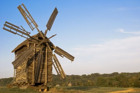 old wooden windmill at sunset