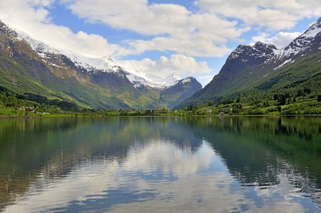 Quiet norway lake surrounding by snow-covered mountains