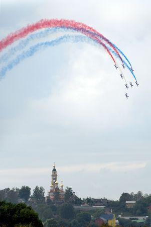 Manmade rainbow above Orthodox church. Aerobatics on Russian  airshow.