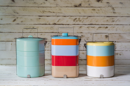 Still life with colorful retro food carrier on wood table background
