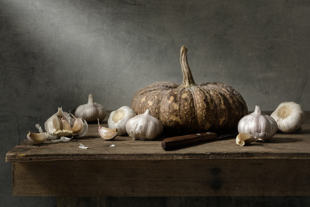 fine wood: Still life with garlics and pumpkin on wood table